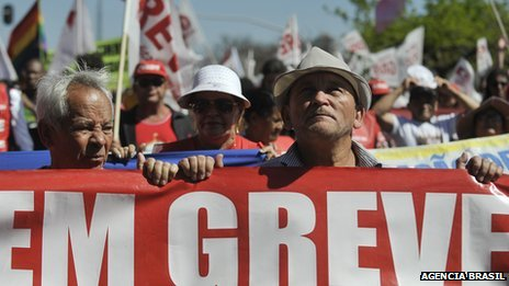 "Striking public sector workers in Brazil hold up sign saying ""On strike"""