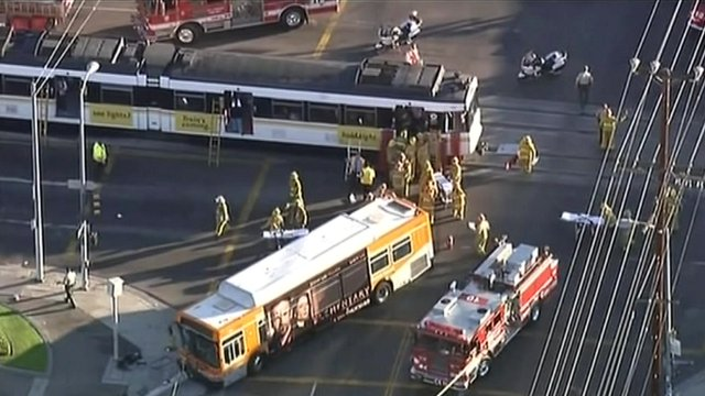 Bus and light rail service surrounded by fire engines at the scene of the collision