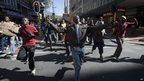 Young people run through the city streets of Cape Town as part of a march organised by the ANC Youth League on August 27