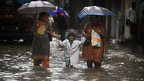 Indian pedestrians walk through a flooded street during heavy rains in Mumbai.