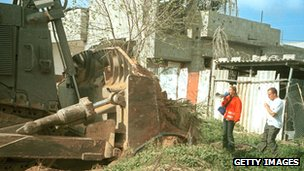Rachel Corrie stands between an Israeli bulldozer and a Palestinian house on 16 March 2003 in the Rafah refugee camp in the Gaza Strip on 16 March 2003