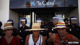 Members of the Andalusian Union of Workers (SAT) protest in front of Spanish riot police as they guard the entrance of a Caixa bank branch