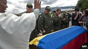 Colombian police officers and relatives pray over coffin of Cristian Flores, who was killed in Farc attack, August 2012