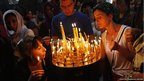 People light candles during a religious service