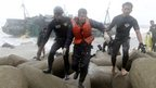 A Chinese fisherman is led to safety by rescue workers