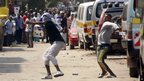Muslim youth throw stones at riot police, outside Masjid Musa Mosque, in Majengo, Mombasa, Kenya, Tuesday, Aug. 28, 2012.