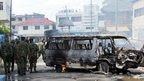 Kenyan security forces next to a burnt vehicle in Mombasa (27 August).