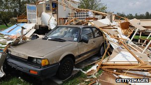 A car sits along debris from a house destroyed by Hurricane Gustav