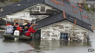 A boat full of people leaves a submerged home in Louisiana