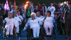 Paralympian Sally Haynes (front) carries the torch with other former Paralympians around the athletics track following the torch relay ceremony at Stoke Mandeville Stadium in Buckinghamshire, 28 August 2012