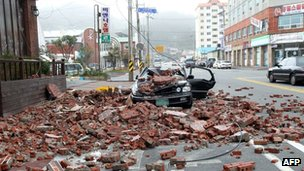 Fallen bricks lie next to a destroyed car in Wando, South Korea, after Typhoon Bolaven hit on 28 August 2012