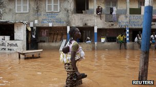 A woman with a baby on her back wades through water after overnight flooding on a street in Senegal's capital Dakar, August 14, 2012