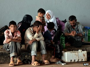 A Syrian family wait to be allowed to cross the Syria-Turkish border (27 August 2012)