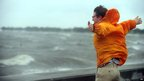 A man leans into the wind next to Lake Pontchartrain in New Orleans (28 Aug 2012)