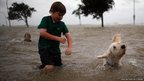 Joshua Keegan and his dog Scout swim in the rising water of Lake Pontchatrain as Hurricane Isaac approaches on August 28, 2012 in New Orleans, Louisiana. Hurricane Isaac is expected to make landfall later today along the Louisiana coast