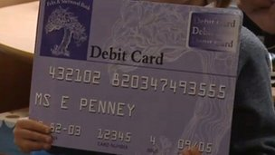 Schoolchild holds a mock debit card