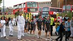 Torchbearer and people walking past a bus garage. Photo: Andrew Pick