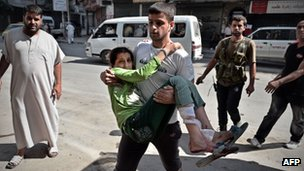 "A Syrian man carries a wounded girl into a hospital in Aleppo, Syria""s second largest city, on August 28, 2012"