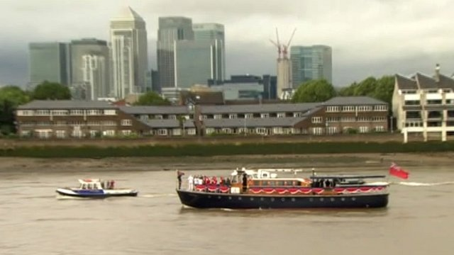 Torch transported on boat in front of Canary Wharf