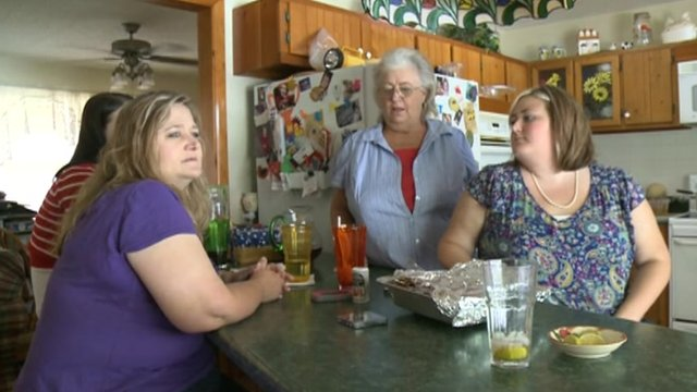 Three women sit at a kitchen table