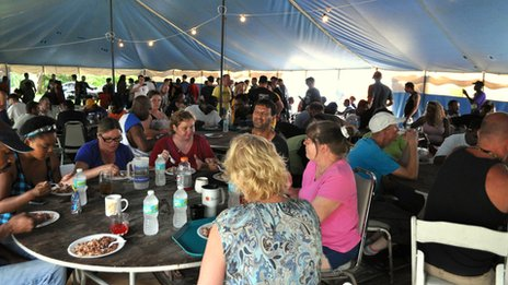 People eating at a feeding area for the homeless in Tampa, Florida 29 August 2012