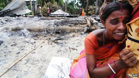 A Indian woman cries near the remains of her house burnt by rioters in Barpeta district in Assam on 29 August , 2012