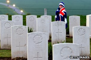 Child wearing Australian flag walks past graves at Australian war memorial in France