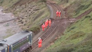 Workmen on the track near the derailed train