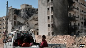 Children ride a flat bed truck in front of bombed-out buildings