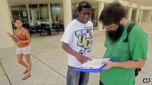Aubrey Marks, left, watches Jordan Allen, center, as he helps student Casey Eirhstaedt, right, register to vote at the University of Central Florida in Orlando, Florida 31 July 2012
