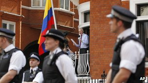 Police officers looks on as Julian Assange reads a statement to the media from the window of the Ecuadorean embassy