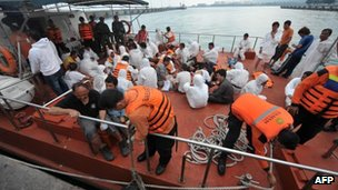 Asylum-seeker survivors are seen onboard an Indonesian rescue boat at Merak seaport on 31 August, 2012