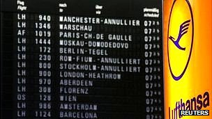 Cancelled flights are seen on a flight schedule board next to the logo of German air carrier Lufthansa at the Fraport airport in Frankfurt