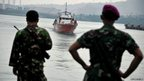 Indonesian marines look towards a rescue boat carrying asylum seekers