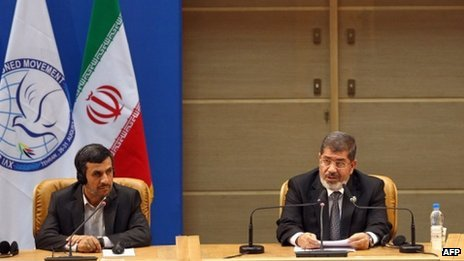 Egyptian President Mohammed Mursi (R) makes his speech at the NAM summit, as Iranian President Mahmoud Ahmadinejad listens