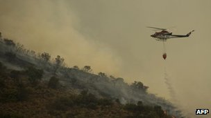 Fire brigade helicopter pours water to extinguish a wildfire in Ojen, 31 Aug