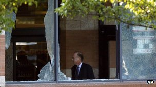 Middlesex County prosecutor Bruce Kaplan is seen through two broken windows at a Pathmark grocery store in Old Bridge, New Jersey 31 August 2012