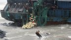 A Chinese fisherman exits a stranded fishing boat