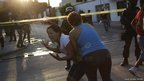 A woman is held back at the scene of a killing in Monterrey