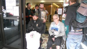 Demonstrators block the door of the DWP office