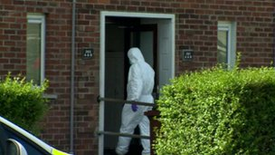 Forensic officer entering house to examine death scene
