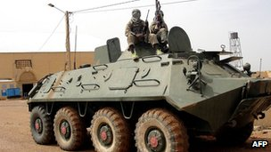 Fighters of the Islamist Movement for Unity and Jihad pose an abandoned Malian army tank in the northern town of Gao on 8 August 2012 (file picture)
