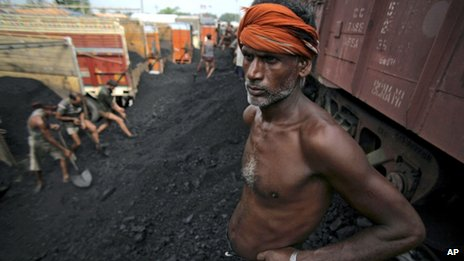 An Indian labourer takes a break, as others load coal onto trucks at a coal depot on the outskirts of Jammu, India,