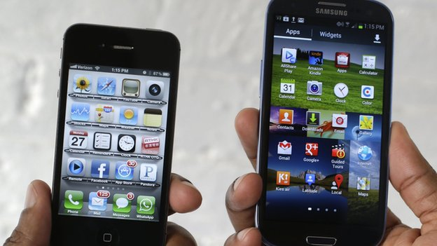 An iPhone is held next to a Samsung Galaxy SIII