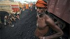 A labourer takes a break as others load coal onto trucks at a coal depot near Jammu on 23 August 2012