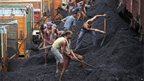Indian labourers load coal onto trucks at a coal depot near Jammu on 23 August 2012