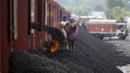 Indian labourers work at a coal depot near Jammu on 23 August 2012
