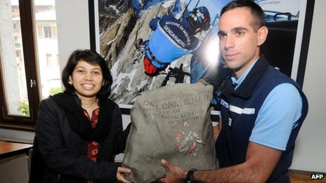 A French official hands over the diplomatic bag to Satwant Khanalia, an Indian embassy official in Paris, on 3 September 2012 in Chamonix, French Alps