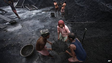 Workers deliver coal at a coal depot in Gauhati, India, Wednesday, Aug. 22, 2012