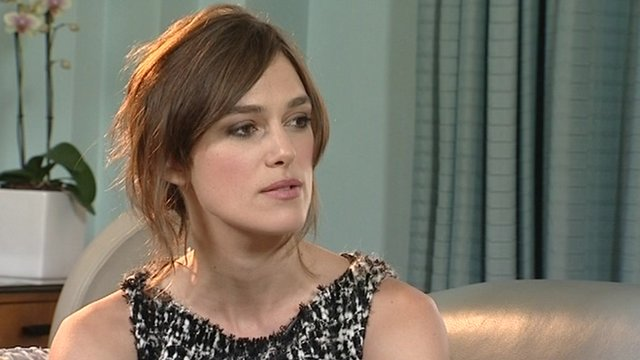 Keira Knightley being interviewed and wearing a black and white dress.